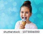 happy little child girl eating...   Shutterstock . vector #1073006000