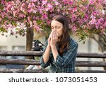 young pretty woman sneezing in...   Shutterstock . vector #1073051453
