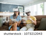 happy couple in vr headsets... | Shutterstock . vector #1073212043