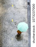 woman with green umbrella is... | Shutterstock . vector #1073237000