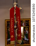 Small photo of Golden, richly decorated Christian cross wrapped in a red stole with the inscription alleluia