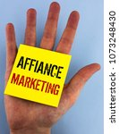 Small photo of Writing note showing Affiance Marketing. Business photo showcasing joining two or more companies in same field mutual goal written on Sticky Note Paper on the plain blue background Hand.
