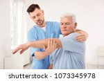 young physiotherapist working... | Shutterstock . vector #1073345978