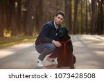 handsome young man with a dog... | Shutterstock . vector #1073428508