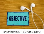 Small photo of Writing note showing Objective. Business photo showcasing Goal planned to be achieved Desired target Company mission written on Sticky Note Paper on wooden background Handsfree next to it.