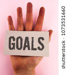 Small photo of Conceptual hand writing showing Goals. Business photo text Desired Achievements Targets What you want to accomplish in the future written on Cardboard Piece placed on the Hand on plain background.