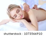 young woman lying on a massage... | Shutterstock . vector #1073566910