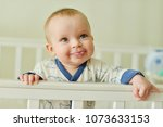 funny baby standing in the bed... | Shutterstock . vector #1073633153
