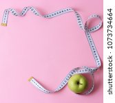 Small photo of apple and centimeter tape on a colored background with a place for inserting the text. minimalism, top view. concept diet, healthy eating, beautiful body, sports.