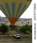 Small photo of Ground crew pulling down a Landing yellow and blue hot air balloon in Cappadocia, Central Anatolia, Turkey.
