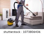 man cleaning sofa in the living ... | Shutterstock . vector #1073806436