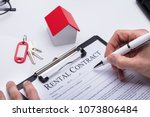 human hand filling rental... | Shutterstock . vector #1073806484