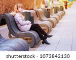 the young girl sits on a bench... | Shutterstock . vector #1073842130