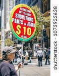 Small photo of Sydney, Australia - Nov 14, 2017: A man holding up a sign on Martin Place, drumming up business for a nearby fabric alteration store. People walking around in the area.