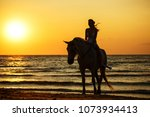 silhouette of a woman at sunset ... | Shutterstock . vector #1073934413