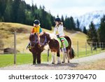 kids riding pony in the alps... | Shutterstock . vector #1073970470