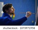 artist in blue sweater paints... | Shutterstock . vector #1073971958