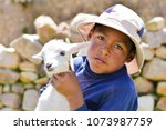 Small photo of Serious native american child with a sheep.