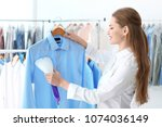 young woman steaming shirt at... | Shutterstock . vector #1074036149