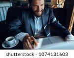 business man smiling  cafe    ... | Shutterstock . vector #1074131603