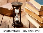 old hourglass with books on... | Shutterstock . vector #1074208190