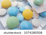 Small photo of Stack of pain pill packets in shades of blue, green and bright yellow, close up medication on white background.
