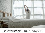 men sit at the edge of the bed. ... | Shutterstock . vector #1074296228