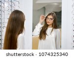 young girl trying on eyeglasses ... | Shutterstock . vector #1074325340