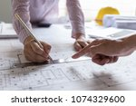 architect working on blueprint... | Shutterstock . vector #1074329600