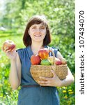 Happy young woman with apple harvest in orchard - stock photo