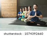 young women and men in yoga... | Shutterstock . vector #1074392660
