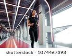 athletic woman with earphones... | Shutterstock . vector #1074467393