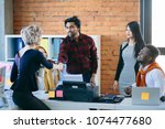 Small photo of multy ethnic team is greeting formally a new member to their crew in thr loft room. salute woman with a smile. acclaim visit. make a deal. clench a bargain