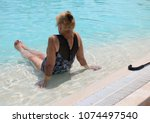 elderly woman in a pool. | Shutterstock . vector #1074497540