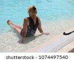 elderly woman in a pool.   Shutterstock . vector #1074497540