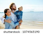 happy family of three embracing ... | Shutterstock . vector #1074565190