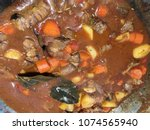 beef stew in pot. stew being... | Shutterstock . vector #1074565940