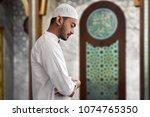 muslim man praying | Shutterstock . vector #1074765350