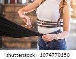 Small photo of Female hairdresser hold in hand lock of hair, scissors closeup. Keratin restoration, latest trend, fresh idea, haircut picking, shorten tips concept