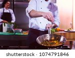 young male chef putting spices... | Shutterstock . vector #1074791846