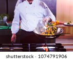 young male chef flipping... | Shutterstock . vector #1074791906
