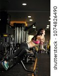 Small photo of Athletic young woman doing hyperextension in the gym. Woman flexing back and abdominal muscles on bench
