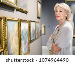 Stock photo glad positive smiling female visitor looking at artwork painting in the museum indoors 1074964490