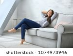 young woman relaxing on cozy... | Shutterstock . vector #1074973946