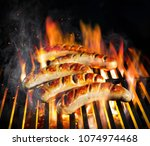 grilled sausage on the flaming... | Shutterstock . vector #1074974468