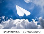 white paper airplane in a blue... | Shutterstock . vector #1075008590