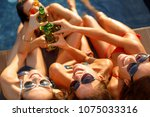 four young women toast with a... | Shutterstock . vector #1075033316