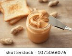 knife with creamy peanut butter ... | Shutterstock . vector #1075066076