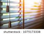 wooden blinds with sun light. | Shutterstock . vector #1075173338