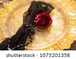 Small photo of The bud of a red rose, lying on a golden plate, next to a black veil, girded with a necklace. Decoration, gothic wedding. Copy space.